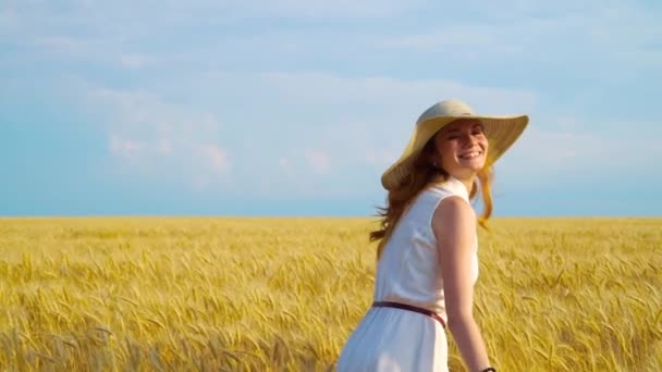 Happy girl in light dress and straw hat walking on wheat field in harvest season