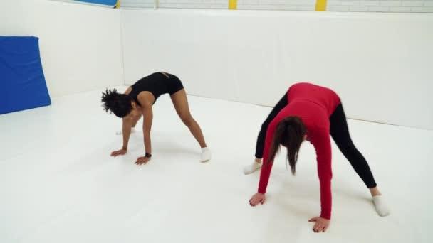 Multiracionális lányok sportruházatban guggoló és nyújtózkodó lábak szőnyegen az edzőteremben