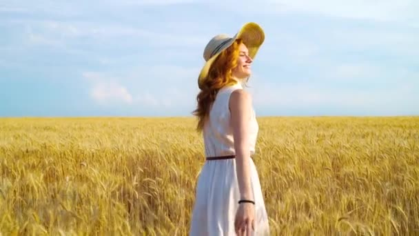 Red haired girl in sumnmer dress and straw hat walking on wheat field
