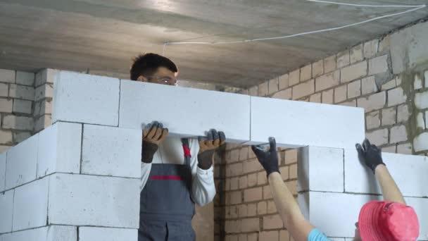 pokládka betonových bloků nad budoucími dveřmi na staveništi