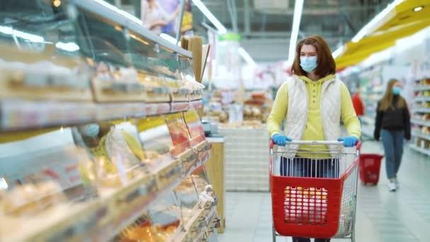Mladá žena v lékařské masce výběr čerstvé pekárny v supermarketu