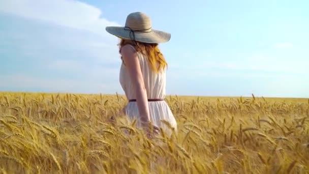 Dívka v bílých šatech a velký klobouk chůze na pšeničném poli
