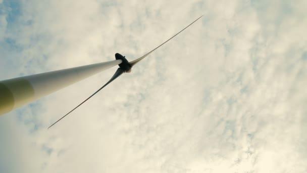 Větrná turbína přes bouřlivé zatažené obloze pomocí obnovitelných zdrojů energie pro výrobu elektrické energie.