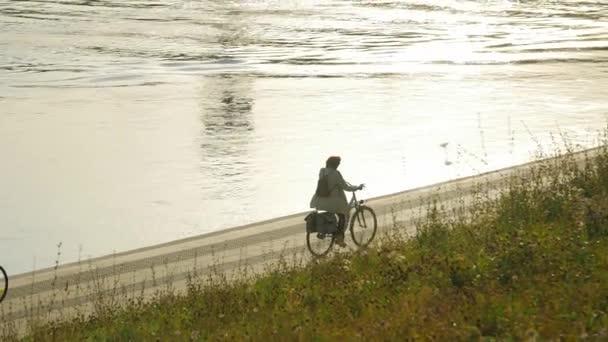 Lidé na koni na kole poblíž řeky v růžový západ slunce, zdravé venkovní životní styl