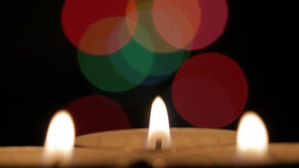 Primo piano tre candele e ghirlande. Priorità bassa vaga con luci colorate