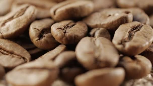 Zblízka se kávová zrna. Před kamerou se otáčí deska s kávová zrna.