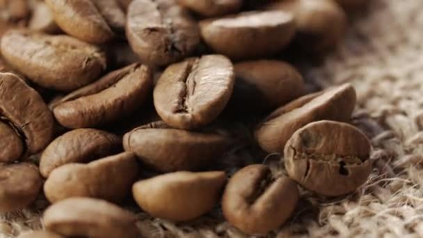 Eine Handvoll von braunen, gerösteten Kaffee Bohnen auf Jute Sackleinen Hintergrund, Nahaufnahme, Drehung