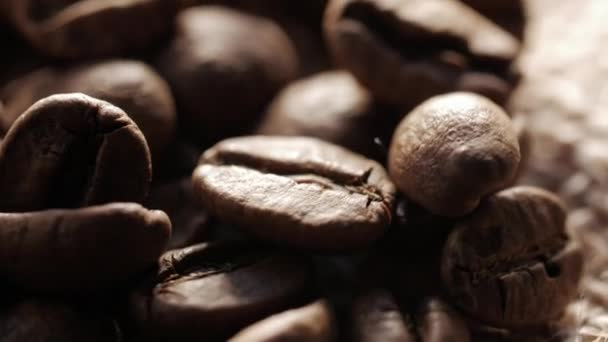 A handful of brown, roasted coffee beans on burlap sacking background, close up, rotation