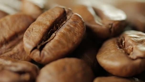 Zblízka se kávová zrna. Před kamerou se otáčí deska s kávová zrna