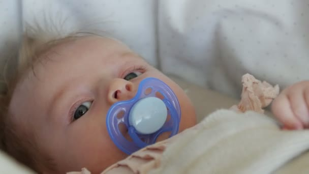 Tříměsíční miminko leží na dece s dudlík. Babys tvář zblízka.