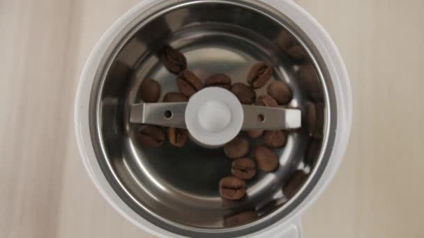Kávová zrna nalil. Pražená zrnková káva nalije do mlýnek na kávu. Detail