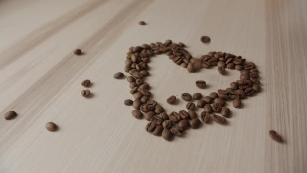 Coffee beans on a wooden table. Background of falling coffee beans. Heart of the coffee beans.