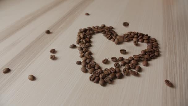 Kávová zrna na dřevěný stůl. Na pozadí klesajících kávová zrna. Srdce z kávových zrn