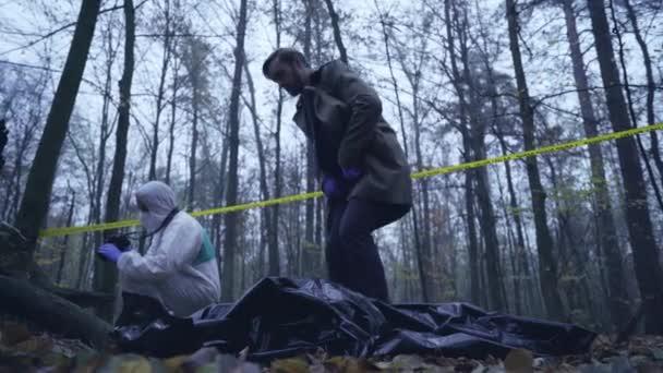 Detektiv se dívá na tělo oběti maniaka, soudní znalci vyšetřující místo činu.
