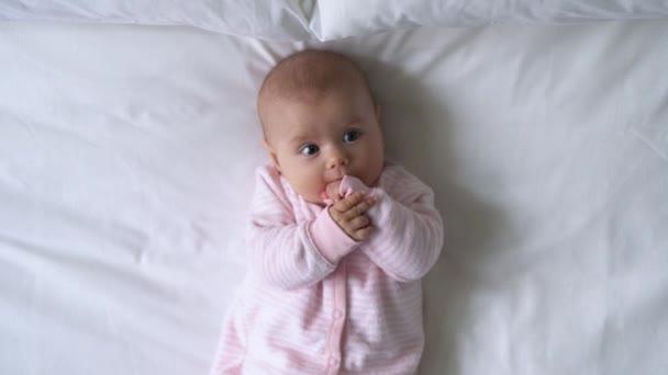 Zvědavá holčička ležící v posteli, strkající malíčky do pusy, rané dětství