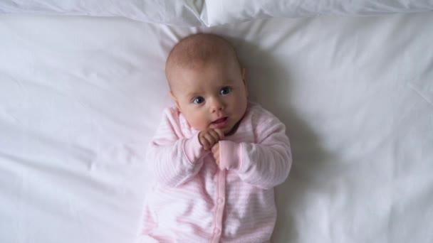 Bájos kis baba fekszik az ágyban, és a kamerába néz, édes kisgyermekkor