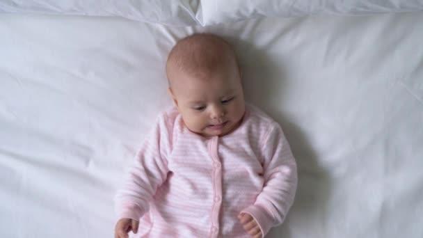Vtipné novorozeně dívající se na kameru, pohybující se malé ručičky a rozhlížející se