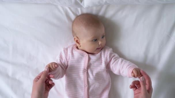 Žena ruce hrát s rozkošným kojencem, baby cvičení a zdravotní aktivity