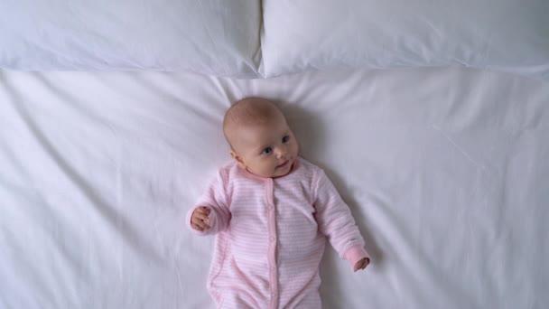 Šťastný úsměv na tváři holčičky, rozkošné dítě ležící na velké posteli, zdravé dětství