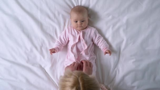 Young mother changing newborn baby clothes, parental care, happy motherhood