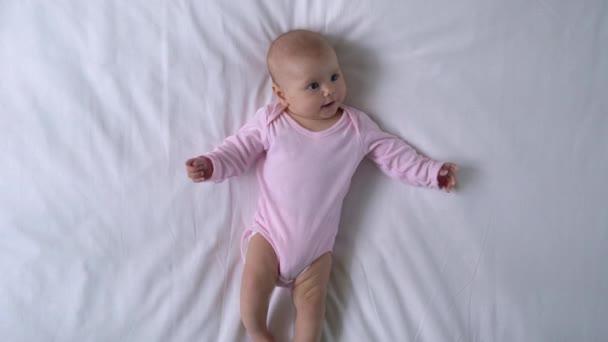 Okouzlující miminko hraje nohy a paže, žvýká sladké malé prsty, šťastné dětství