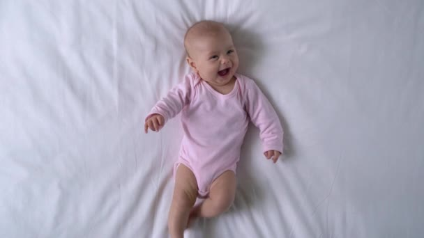 Veselá holčička se směje a rozhlíží, první sladký úsměv na tváři