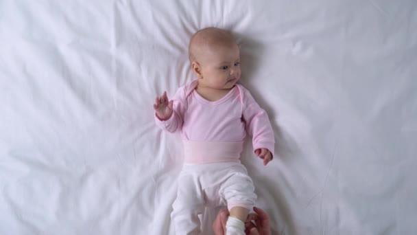 Álmos baba fekszik az ágyon, szerető fiatal anya átöltözik, lefekvés előtt rutin
