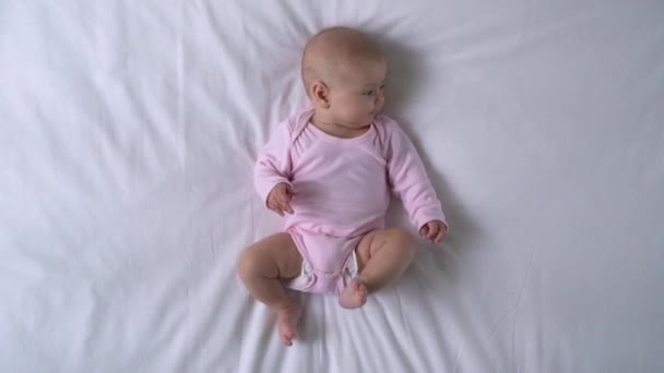 Adorable baby girl actively moving legs and arms on bed, infant health care