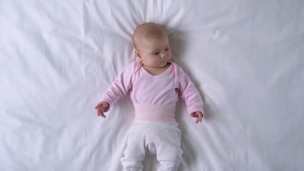 Aktivní dítě se ráno probouzí, zvědavě se rozhlíží a usmívá, dětinství
