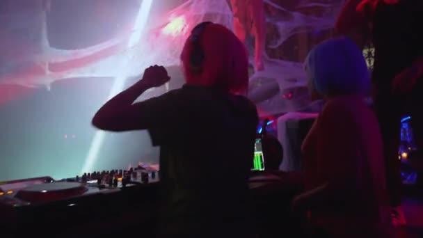 Dva ženské DJ otáčející se ovladače na gramofonu, vystupující na hudební párty