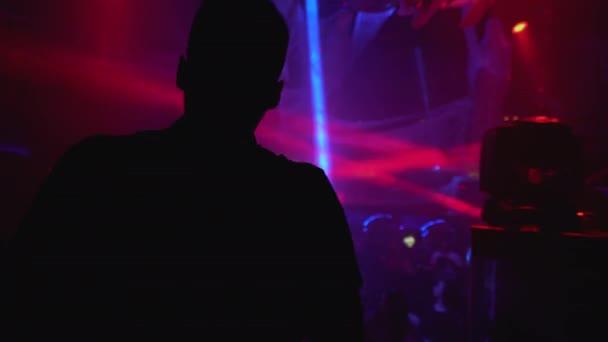 Silueta muže těší noční klub párty, taneční parket osvětlené světly