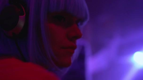 Mladá žena ve sluchátkách tanec na hudbu na párty, dj vystupování v nočním klubu