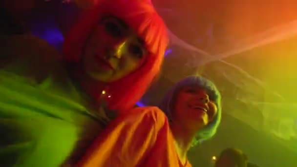 Provokativní dívky tančí na večírku v nočním klubu, usmívají se spolu