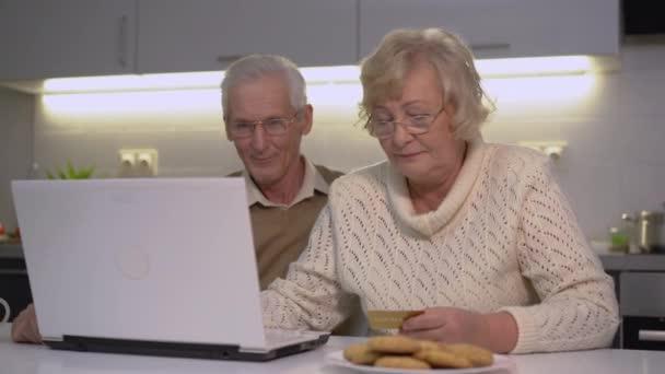 Idősebb pár, akik hitelkártya számot helyeznek el a laptopon, ingatlant vásárolnak.