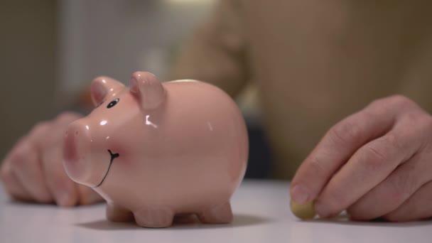 Férfi kéz tesz érmét a malacperselybe az asztalon, pénzügyi befektetés, megtakarítás