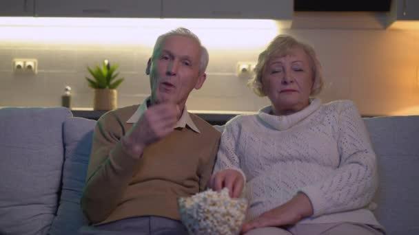 Nyugdíjas férj és feleség filmet néznek a kanapén és popcornt esznek együtt.