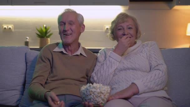 Vidám nyugdíjasok nézik a vígjátékot, nevetnek, popcornt esznek otthon.
