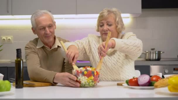 Aktív idős pár főzés egészséges étel együtt otthon, mosolygós és beszél