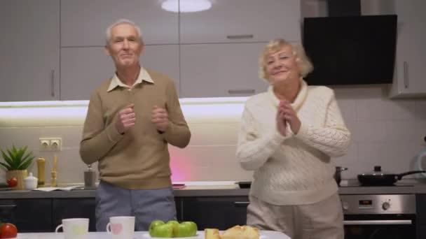 Vicces idős pár táncolnak együtt otthon, élvezik az aktív és egészséges életet