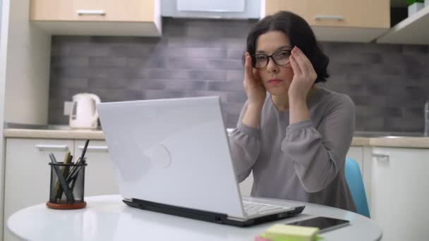 Female accountant putting on eyeglasses, working on financial report at home
