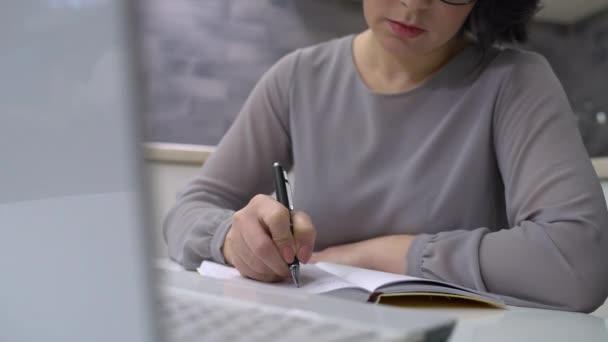 Csinos női írás jegyzetfüzetben, asztalnál ülve, üzleti tervező, jegyzetek