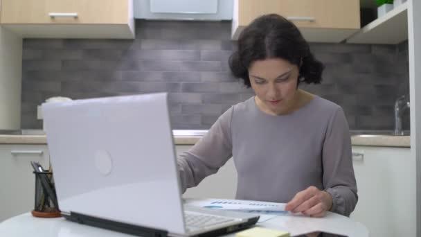 Středního věku účetní připravit finanční zprávu, psaní na notebook doma