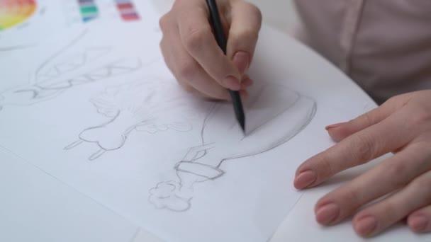 Talentovaná žena kreslí kresby oděvů tužkou, pracuje v kanceláři, design