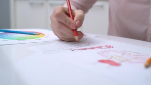 Woman working on sketch of a dress, sitting at table, creative job, startup