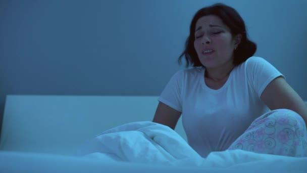 Kranke Frau reibt sich Bauch, leidet nachts unter scharfen Bauchschmerzen, Verdauungsstörungen