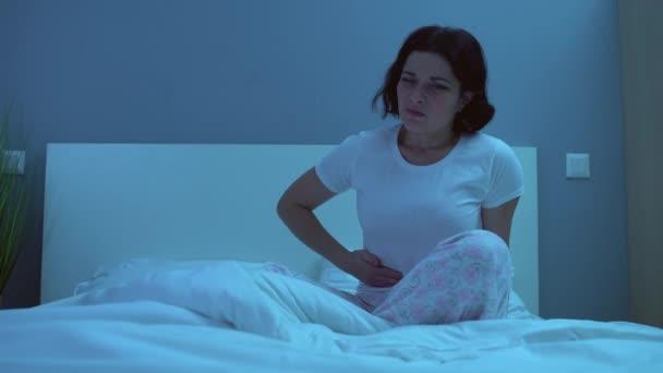 Nešťastná žena má bolestivé menstruační křeče, tření břicha v posteli v noci