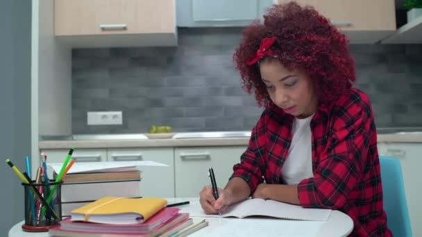 Komoly vegyes fajú diákok írása jegyzetfüzetbe, felkészülés az iskolai órákra