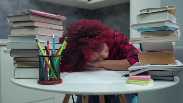 Vyčerpaná studentka spící na stole, unavená z domácího úkolu