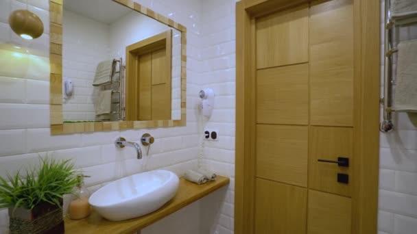 Moderní koupelna interiér, bílé umyvadlo a zrcadlo na zdi, hotelový servis