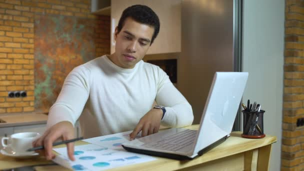 Financial expert analyzing sales report, examining diagrams, man working at home